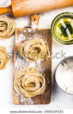 Raw uncooked fresh pasta nest on marble table.