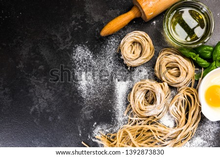 Raw uncooked homemade pasta ingredients, border background.