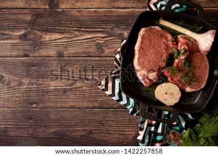 Raw uncooked lamb meat chops with rosemary and garlic in black iron grilling pan, top view, horizontal composition.