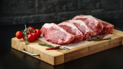 Raw uncooked meat steak striploin new york on a wooden board with tomatoes and rosemary, side view, horizontal