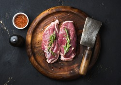 Raw uncooked poultry meat cut. Duck breast with rosemary, spices and butcher cleaver on dark wooden tray over black wooden background, top view