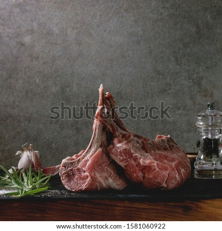 Raw uncooked rack of lamb on wooden cutting board with salt, herbs rosemary, pepper and garlic on grey table cloth as background. Dark still life