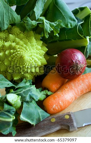 Raw uncooked Romanesco broccoli, carrots and onion on a chopping board