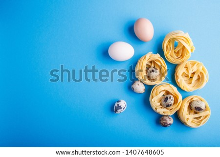 Raw uncooked tagliatelle pasta with quail eggs on a blue pastel background. top view. copy space. flat lay.