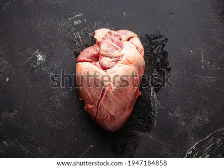 Raw uncooked whole beef or pork heart on black rustic stone background from above, offal and variety meats Foto stock ©