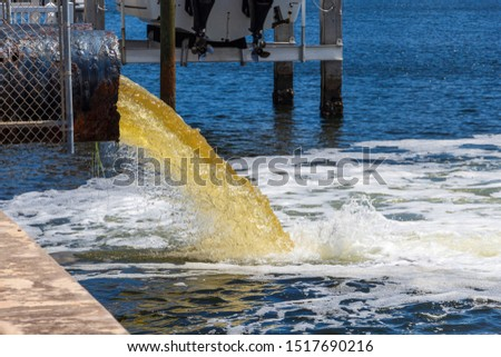 Raw untreated yellow water or sewage being pumped into a blue lake - Hollywood, Florida, USA