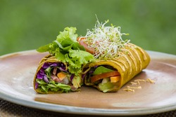 Raw vegan carrot and cumin wrap roll stuffed with shred lettuce, tomato, avocado, spinach and savory zucchini hummus . Island Bali, Ubud, Indonesia