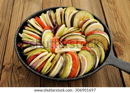 Raw vegetables layed for ratatouille made of eggplants, squash, tomatoes and onions in black cast iron pan on wooden table horizontal