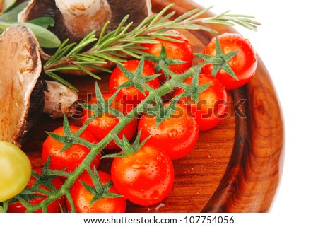 raw vegetables on dark wood plate over white - stock photo