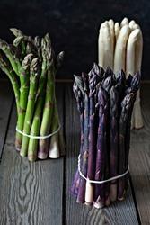 Raw white, purple, green asparagus on a dark wooden background.