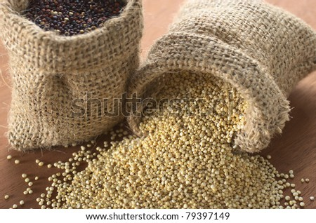 Raw white quinoa grains in jute sack on wood with red quinoa in another sack standing (Selective Focus, Focus on the white quinoa at the opening of the sack) - stock photo