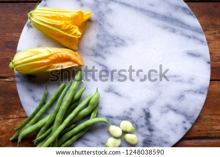 raw yellow courgette flowers, green beans and broad beans on a white and blue marble chopping board, the vegetables are arranged on the left side of the image leaving space on the right side
