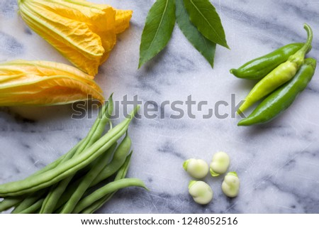 raw yellow courgette flowers, green beans and broad beans on a white and blue marble chopping board, the vegetables are arranged on the left side of the image leaving space on the right side of the bo