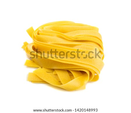 Raw yellow italian pasta pappardelle, fettuccine or tagliatelle close up. Egg homemade dry ribbon noodles, long rolled macaroni or uncooked spaghetti isolated