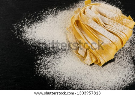 Raw yellow italian pasta pappardelle, fettuccine or tagliatelle close up. Egg homemade noodles cooking process, long rolled macaroni or uncooked spaghetti on black stone background