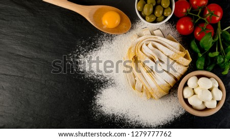Raw yellow italian pasta pappardelle, fettuccine or tagliatelle close up with eggs. Egg homemade noodles cooking process, long rolled macaroni or uncooked spaghetti on black stone background top view