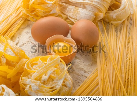 Raw yellow italian pasta pappardelle, fettuccine or tagliatelle close up with eggs. Egg homemade noodles cooking process, long rolled macaroni or uncooked spaghetti on light table background