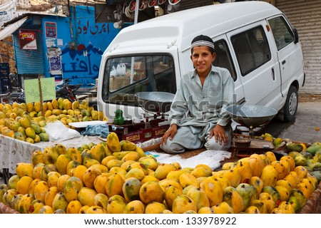 RAWALPINDI, PAKISTAN - JULY 16: Unidentified Pakistani boy sells fruits at Raja Bazaar on July 16, 2011 in Rawalpindi, Pakistan. Raja Bazaar is the main shopping area in Rawalpindi.