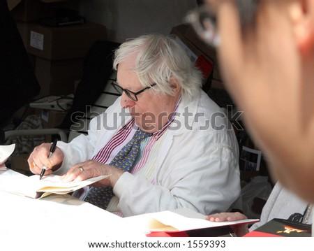 Ray Bradbury signing a book.