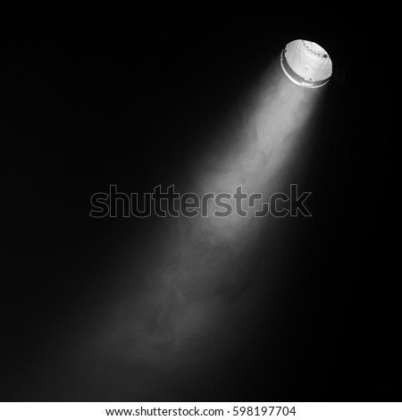 Shutterstock Ray of scenic spot light over black smoky background, square stage illumination background photo