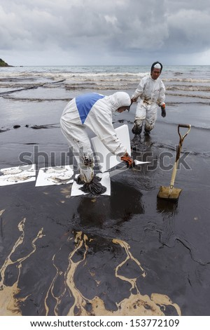 Rayong, Thailand - July 31, 2013: Worker in Biohazard suit placing absorbent paper in a clean-up operation of crude oil spilled at Ao Prao Beach on July 31, 2013 in Koh Samet, Rayong, Thailand. - stock photo