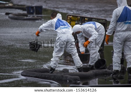 RAYONG, THAILAND - JULY 31, 2013: Workers wearing biohazard suits scoop a pail full of spilled crude oil as cleaning operations from a beach of Samet Island on July 31, 2013 in Rayong, Thailand. - stock photo