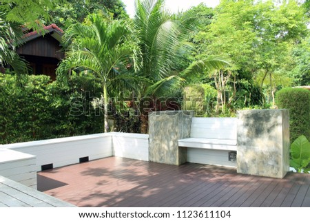 Rayong, Thailand - June 24th, 2018: A raised terrace area with decking and concrete walls sits in the middle of a tropical garden in the grounds of Ban Chom Resort on Koh Samed Island, Rayong. #1123611104