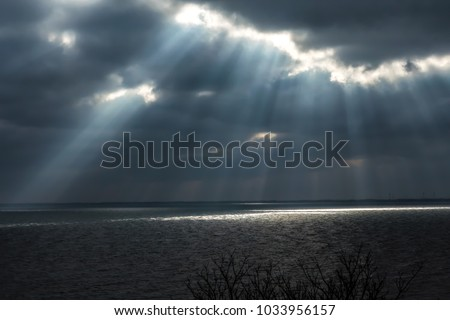 Rays of light shining through storm clouds.