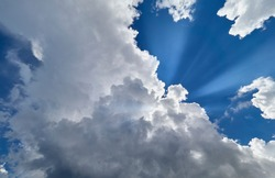 Rays of sun by mighty cloud against the blue sky