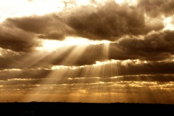 Rays of sun filter through the clouds of a Texas sky