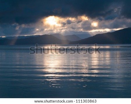 Rays of sun shining through the clouds and sunset over water