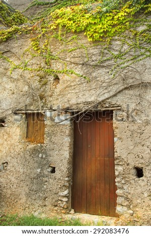 Rays of sunlight on the facade of an old house in the village. The facade of the old house. The door and stone wall.