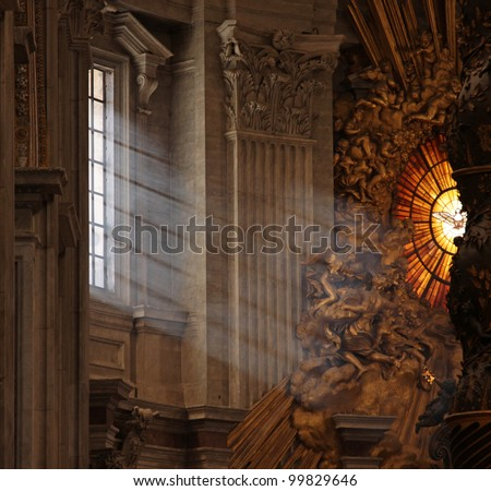 Rays of sunlight shine in the window onto the main altar of St. Peter's Basilica, in Rome, Italy.