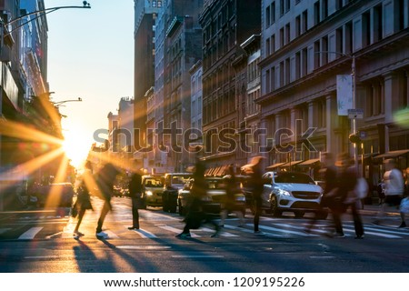 Rays of sunlight shine on the busy people walking across an intersection in Midtown Manhattan in New York City NYC stock photo
