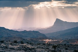 Rays of sunlight shine through scattered clouds on a small arabian village in Jebel Shams mountains, Oman. Epic sunlight in arabian desert.