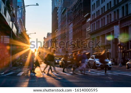 Rays of sunset shine on the diverse crowds of people walking through a busy intersection in Midtown Manhattan New York City NYC stock photo