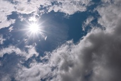 Rays of sunshine breaks through the dark clouds. Sun and blue sky with clouds.Concept of hope for the best, mood changes, enthusiasm, optimism,the breakthrough goal.blue sky and sun.