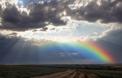 Rays of the sun breaking through the stormy sky, forming a marvelous rainbow