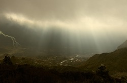rays through the cloud in thunderstorm under the village