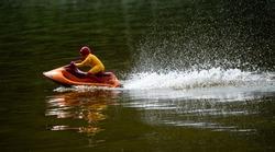 RC controlled jet ski model on lake.