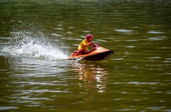 RC controlled jet ski model on lake. Active summer vacation for school child.