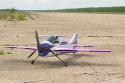RC-Model airplane with remote control. Model aircraft for acrobatics. The model stands on the runway of the airfield.