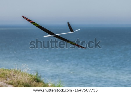 Photo of  RC remotely controlled soaring plane model sailplane on blue sky in brisk wind