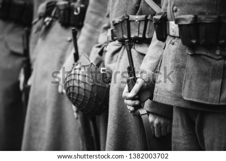 Re-enactors Dressed As World War II German Wehrmacht, Soldiers Standing Order With Rifle Weapons In Hands. Photo In Black And White Colors. Soldiers Holding Weapon Rifles. #1382003702