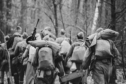 Re-enactors Dressed As World War II Russian Soviet Red Army Soldiers Marching Through Forest In Autumn Day. Photo In Black And White Colors. Soldier Of WWII WW2 Times.