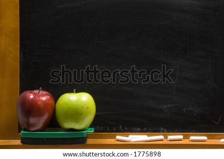 rea and green apple on chalkboard ledge at school, add text to chalkboard