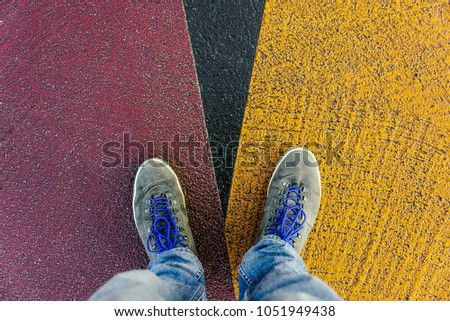 Reaching a crossroads having to decide about past, now and future symbolized by two feet and shoes standing on two different colors on pathway from above Stock foto ©