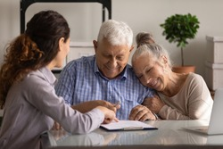 Reaching an agreement. Happy old spouses visiting lawyer broker realtor to buy real estate sign insurance policy create will. Excited aged married couple clients sign financial deal with bank manager