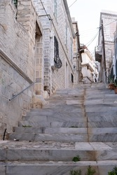 Reaching Ermoupoli capital Chora Syros island Greece by empty traditional narrow old stone marble stairs between stonewall buildings summer sunny day. Bellow to upper view resort destination. Vertical