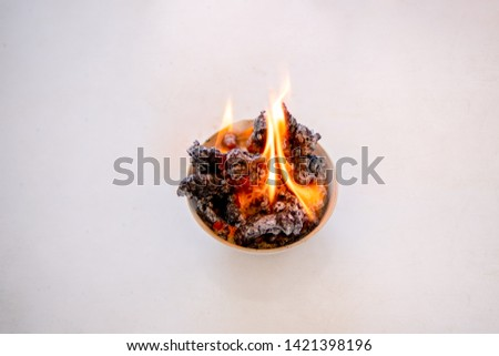 Reaction chemical chemistry concept, combustion reaction, fire flame burning chemistry reagents on crucible on white background, baking powder or sodium bicarbonate and sugar is science show activity